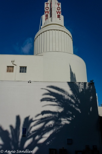The shadow of palms fall on the theater's side wall.
