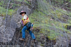 Workers were putting up netting to keep rocks from falling onto the road.