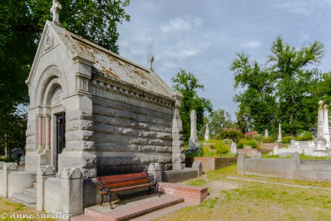 A bench by a mausoleum.