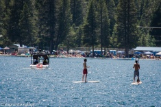 Paddle boarders and crowds on the beach.