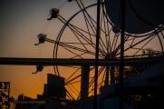 The sun setting behind a ferris wheel.