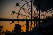 The sun setting behind a ferris wheel.