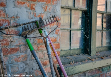 Tools leaning against an old building. Notice the cobwebs on the window sill.