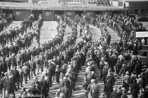A black and white picture of workers entering the shipyard.