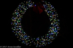 This was a wreath that was hanging from a wire going across the street. Below it, was a string of lights. The following zooms are of this wreath.